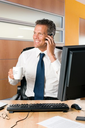 Mature businessman with mobile and a cup of coffee in his modern office Stock Photo - 8235254