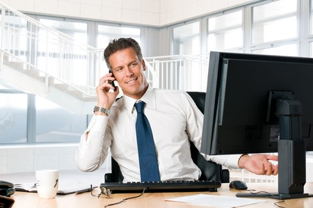 Succesful businessman sit at his desk while talking on mobile Stock Photo - 8235227