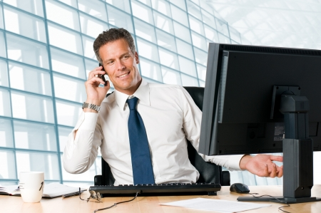man with phone: Successful businessman sit at his desk while talking on mobile in office