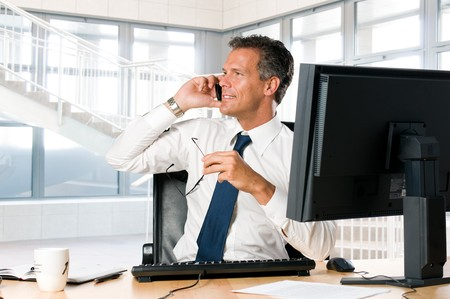 Succesful businessman sit at his desk while talking on mobile photo