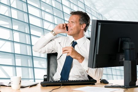 talking businessman: Successful businessman sit at his desk while talking on mobile in office