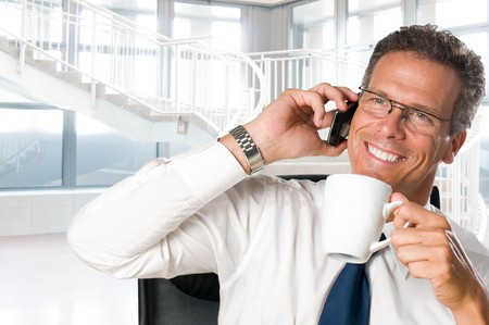 Mature businessman taking a break with a cup of coffee in his modern office photo