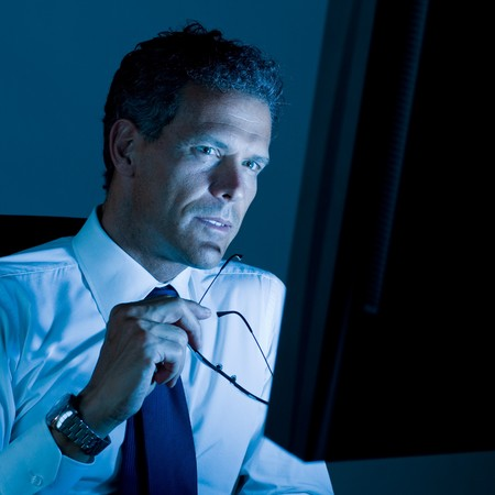 absorbed: Mature businessman working late at night in his office