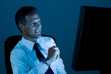 hard look: Mature businessman working late at night in his office