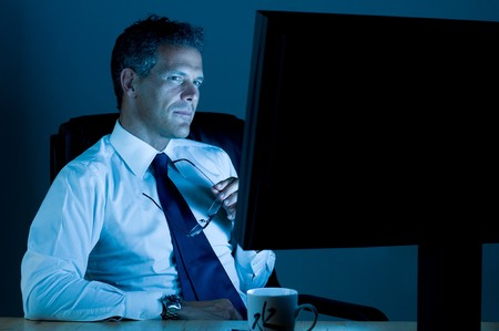 late: Mature businessman working late at night in his office
