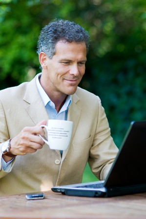 Satisfied businessman working on laptop outdoor while drinking a mug of coffee photo
