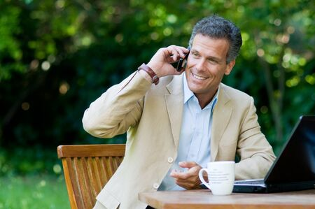 Happy businessman talking on mobile while working outdoor photo