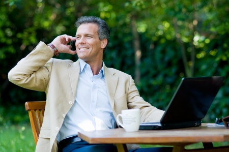 guy with laptop: Healthy mature businessman working outdoor with mobile and laptop Stock Photo