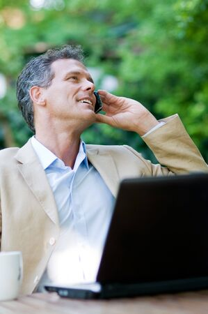 Smiling relaxed businessman talking on mobile outdoor Stock Photo - 8235197