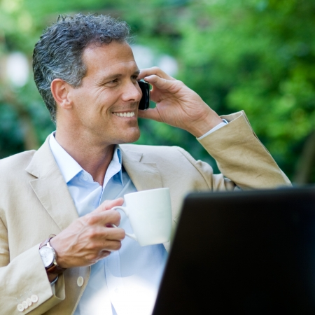Healthy mature businessman working outdoor with mobile and laptop while drinking a mug of coffee photo