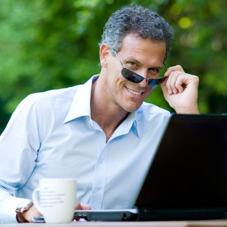 Satisfied businessman looking at camera through a pair of sunglasses photo