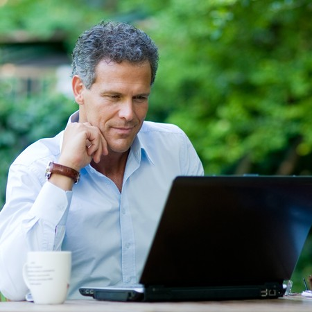 absorbed: Satisfied businessman working on laptop with internet wireless