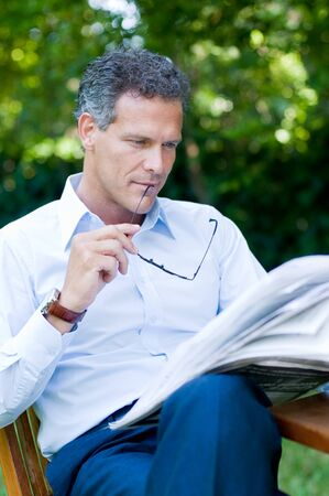 Handsome mature man reading news outdoor during a break, while holding a pair of glasses Stock Photo - 8235263