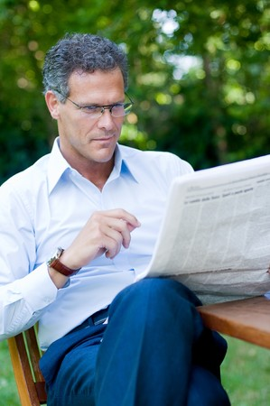 reading glasses: Mature man reading a newspaper outdoor