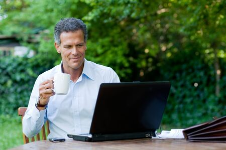 satisfied: Satisfied businessman relaxing outdoor while drinking a mug of coffee