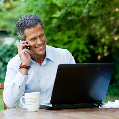Businessman working outdoor with mobile and laptop Stock Photo