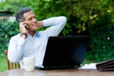 Businessman relaxing outdoor while working with mobile and laptop Stock Photo - 8235179