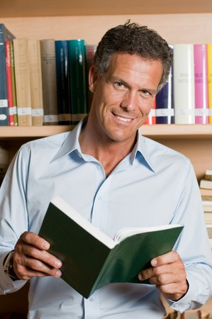 1 mature man: Mature man reading a book in a library. Looking at camera with confidence. Stock Photo