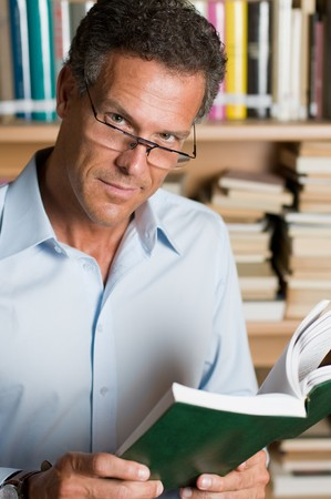 Mature man reading a book with glasses in a library. Looking at camera with confidence. Stock Photo - 8235260
