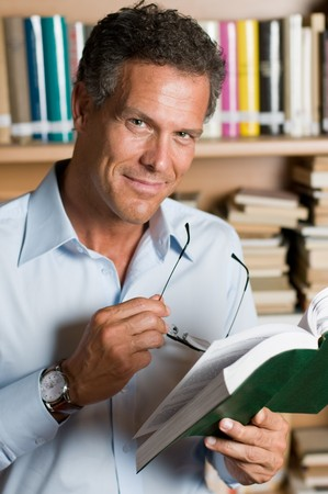 Mature man reading a book with glasses in a library. Looking at camera with confidence. photo
