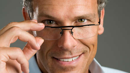 Handsome mature man putting on a pair of modern glasses Stock Photo