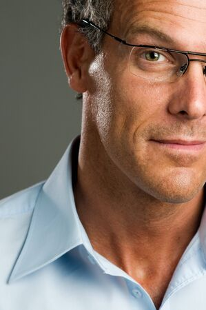 Portret van half volwassen man op zoek naar camera met een paar glazen.