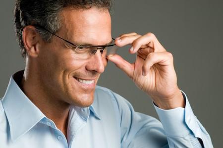 honestidad: Apuesto hombre maduro sosteniendo un par de lentes modernas