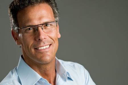 mature adult men: Uomo maturo, guardando alla telecamera con un sorriso luminoso e un paio di occhiali. Spazio per il testo