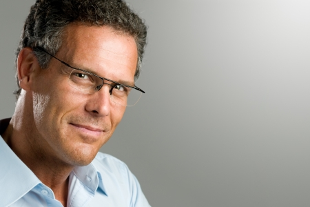 man glasses: Handsome mature man looking at camera with a pair of modern glasses