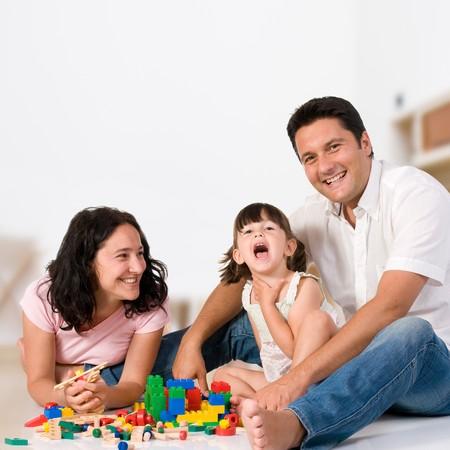 Familia feliz con los padres y la hija jugando con bloques de colores en el interior como en casa Foto de archivo