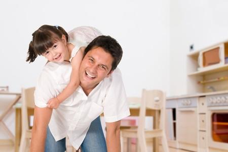 padre e hija: Padre sonriente llevando sobre sus hombros a su peque�a hija en casa  Foto de archivo