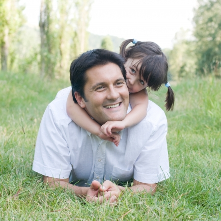 Little cute girl embracing her father outdoor in a park photo