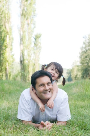 Little cute girl embracing her father outdoor in a park Stock Photo - 8235267