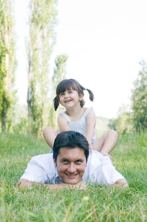 Sweet cute girl sit on the back of her father during a day outdoor Stock Photo - 8235217