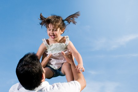 Father throw in air his little daughter in a clear blue sky with copy space for your text photo