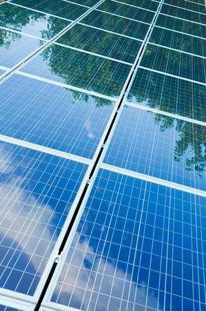 Green trees and blue sky reflection on solar panels. Go green with renewable energy! photo