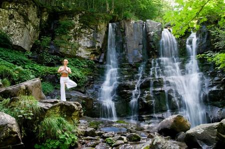 cascades: Bella donna giovane facendo yoga in una splendida foresta vicino a cascata