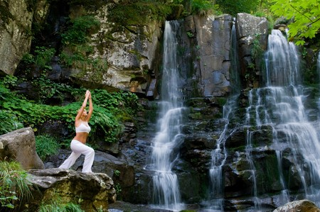 Beautiful young woman doing yoga in a wonderful forest near waterfall photo