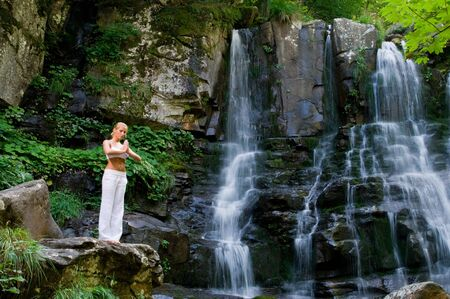 Beautiful young woman meditating while doing yoga in a wonderful forest near waterfall photo