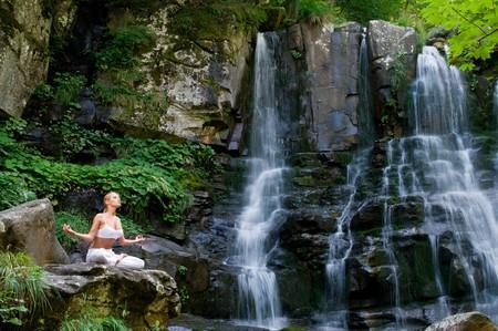 descansando: Joven y bella mujer meditando en posición de loto mientras hace yoga en un maravilloso bosque cerca de cascada  Foto de archivo