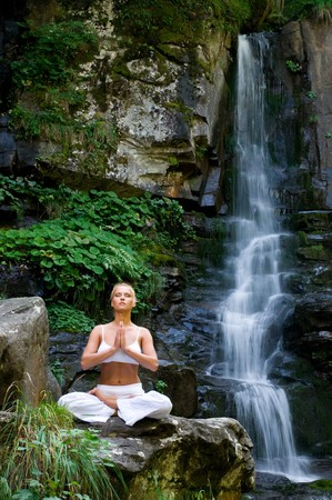 position: Beautiful young woman meditating in lotus position while doing yoga in the nature near waterfall