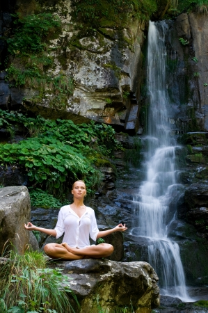 Beautiful young woman meditating in lotus position while doing yoga in the nature near waterfall photo