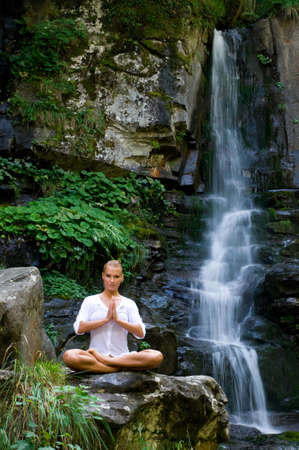 mujer meditando: Joven y bella mujer meditando en posici�n de loto mientras hace yoga en la naturaleza cerca de cascada