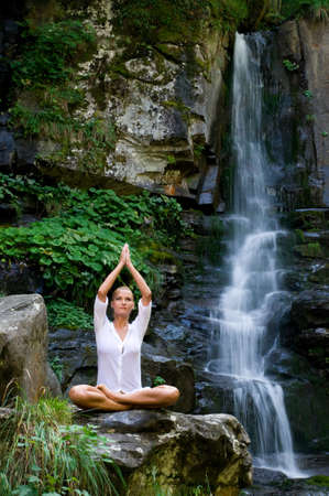 Beautiful young woman meditating in lotus position while doing yoga in the nature near waterfall Stock Photo - 8235415