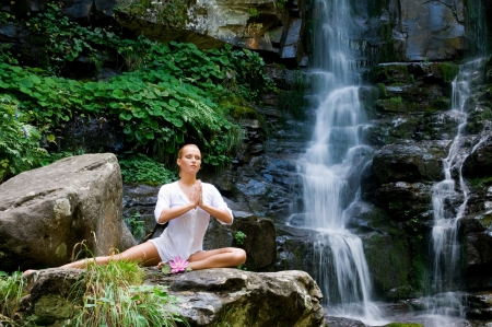 Beautiful young woman meditating with a lotus flower while doing yoga in a wonderful forest near waterfall photo