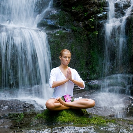 serene: Beautiful young woman meditating in lotus position while doing yoga between waterfalls
