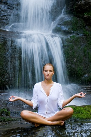 position: Beautiful young woman doing yoga in lotus position near waterfall Stock Photo