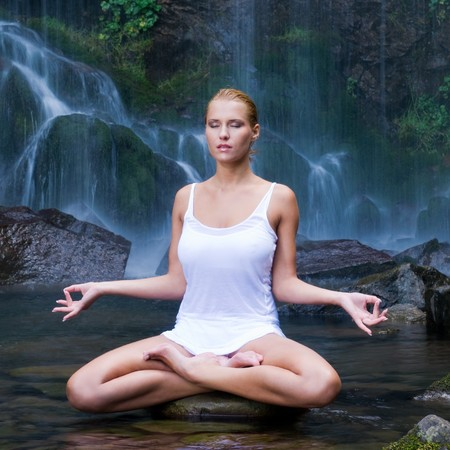 breath: Beautiful young woman doing yoga in a water pool near waterfall