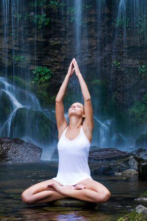 Beautiful young woman doing lotus position yoga in a water pool near waterfall photo