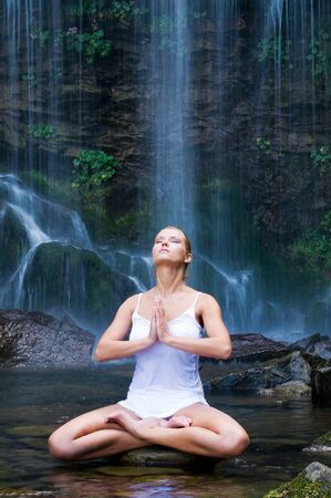 position: Beautiful young woman doing lotus position yoga in a water pool near waterfall